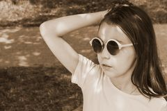 Little girl in sunglasses with loose hair, toned royalty free stock image