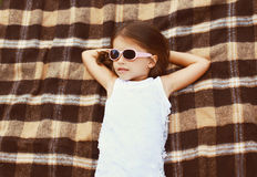 Little girl in sunglasses lying on the plaid Stock Photos