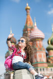 The little girl in sunglasses near the cathedral sitting Royalty Free Stock Image