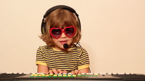 Little girl with sunglasses play music Stock Photos