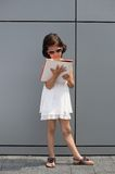Little girl with sunglasses reading a magazine Royalty Free Stock Image