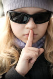 Little girl in sunglasses shows silence sign Stock Image