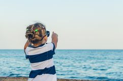 A little girl in sunglasses shows on something with her hand royalty free stock photography