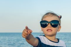 A little girl in sunglasses shows on something with her hand stock photography