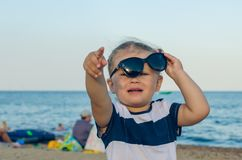 A little girl in sunglasses shows on something with her hand royalty free stock image