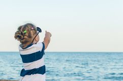 A little girl in sunglasses shows on something with her hand royalty free stock images