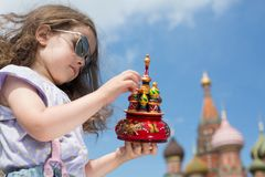 Little girl in sunglasses and suspenders with a miniature cathedral. Near the Kremlin stock image