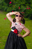 Little Girl with sunglasses. Vintage dressed little girl with sunglasses and falling flower petals Royalty Free Stock Images