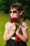 Little Girl with sunglasses. Vintage dressed little girl with sunglasses and red flower Royalty Free Stock Images