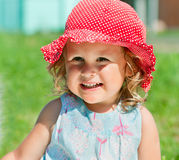Little girl in sunhat. Portrait of smiling little girl in red sunhat outdoors Royalty Free Stock Photos