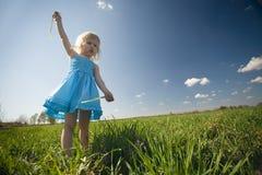Little girl on sunny meadow stock photo