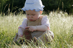 Little girl on sunny meadow. Little girl is sitting on the sunny meadow and busy with her own business Royalty Free Stock Photos
