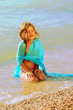 Little girl in a sunset light. Sits in surfing water Royalty Free Stock Photography