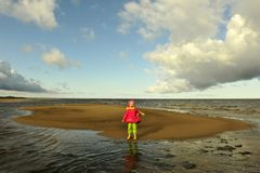 Little girl  on a sunset sandy autumn beach. Stock Photography