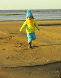 Little girl on a sunset sandy autumn beach. Stock Images