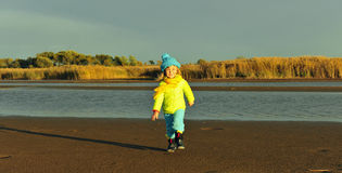 Little girl  on a sunset sandy autumn beach. Royalty Free Stock Image