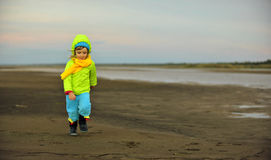 Little girl  on a sunset sandy autumn beach. Royalty Free Stock Images
