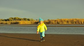 Little girl  on a sunset sandy autumn beach. Royalty Free Stock Photo