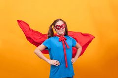Little girl in super hero costume ready to save the world from bad guys over yellow background. Happy kid. Playing superhero stock photos