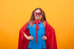 Little girl in super hero costume ready to save the world from bad guys over yellow background. Happy kid. Playing superhero royalty free stock photos