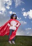 Little girl superhero against blue sky Stock Image