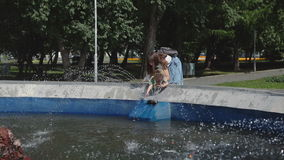 The little girl supported by her mother, wets his hands in the fountain. stock footage