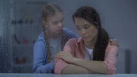 Little girl supporting depressed mother after divorce, break up, rainy weather. Stock footage stock video