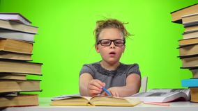 Little girl with surprise that it is in the book. Green screen. Slow motion stock video footage