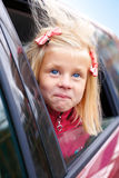 Little girl surprise stares out of the car. On the street Royalty Free Stock Photos