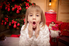 Little girl surprised  on a Christmas background Royalty Free Stock Image