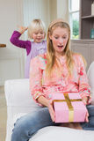 Little girl surprising her mother with gift Stock Images