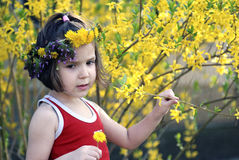 Little girl surrounded by flowers. Little girl with flowers on her head surrounded by yellow flowers Stock Photos