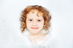 Little girl surrounded soap suds. Happy little girl surrounded soap suds Royalty Free Stock Image