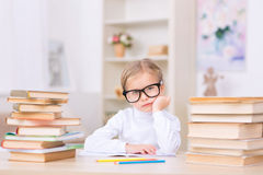 Little girl surrounded by two piles of books. Lots of homework. Little girl in eyeglasses is looking tired while sitting at the desk loaded with two big piles of Stock Photo