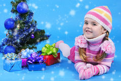 Little girl in a sweater and a hat with the snow Stock Photography