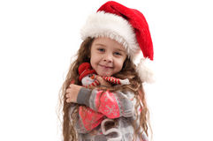 Little girl in a sweater holding a Christmas toy Stock Images