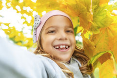 Little girl in sweater with yellow maple leaves Royalty Free Stock Images