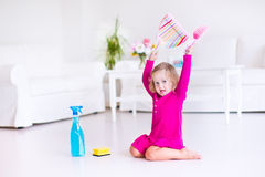 Little girl sweeping the floor. Young happy mother and her little daughter, cute toddler girl, cleaning the house together sweeping the floor in a white sunny Stock Photo