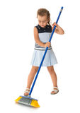 Little girl sweeping. Lovely little girl in a short blue dress sweeping the floor diligently - Isolated on white background Royalty Free Stock Image