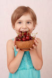 Little girl with sweet cherries. Little girl with a bowl of sweet cherries royalty free stock image
