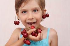 Little girl with sweet cherries. Little girl eating sweet cherries Stock Photography