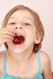 Little girl with sweet cherries. Little girl eating a cherry royalty free stock image