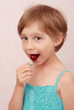 Little girl with sweet cherries. Little girl eating a cherry stock images