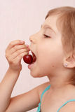 Little girl with sweet cherries. Little girl eating a cherry royalty free stock photos