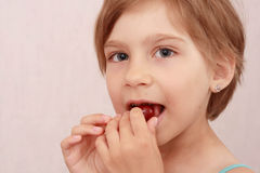 Little girl with sweet cherries. Little girl eating a cherry royalty free stock photography