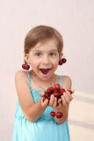 Little girl with sweet cherries. Little girl with handful of cherries stock photo