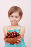 Little girl with sweet cherries. Little girl offering a bowl of cherries stock image