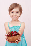 Little girl with sweet cherries. Little girl offering a bowl of cherries stock photos