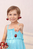 Little girl with sweet cherries. Smiling little girl with handful of cherries royalty free stock photos