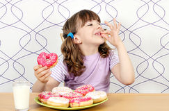Little girl with sweet donuts. Little girl enjoy sweet donuts stock photo